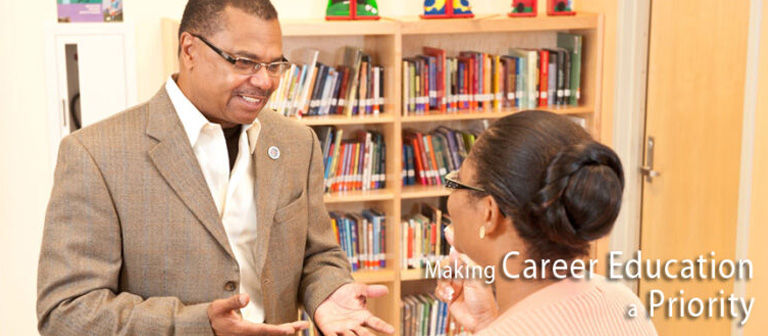 Holmes, Jr. discussing education priorities with classroom teacher